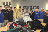 Members of the men's soccer team and Coach Perry Nizzi with some of the hoodies, sweaters and sweatshirts they collected for the Rome Rescue Mission.