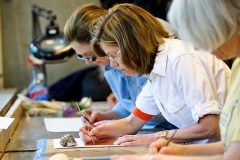 Jane McAllister '77, rear, and Sara Jolin Bedford '77 etch their designs into a copper plate during the printmaking workshop.
