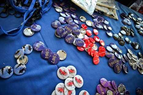 Buttons representing the visiting reunion classes lay out at a table at registration.