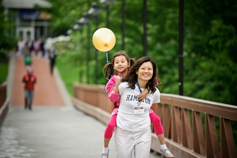 Yully Cha Leonardi '97 carries her daughter, 6-year-old Camen across the bridge to watch the Reunion Parade as part of Reunion Weekend.