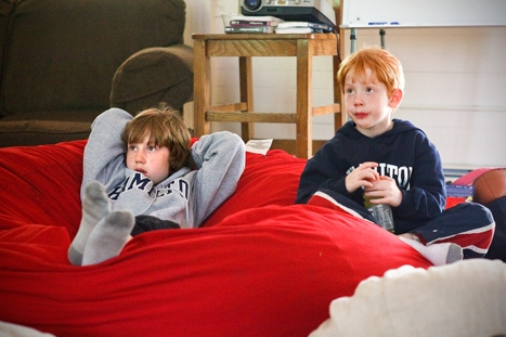 Avi Levey , 9, left, and his brother Ikey, 7, watch a movie while at kid's camp on Saturday, June 2, 2012.
