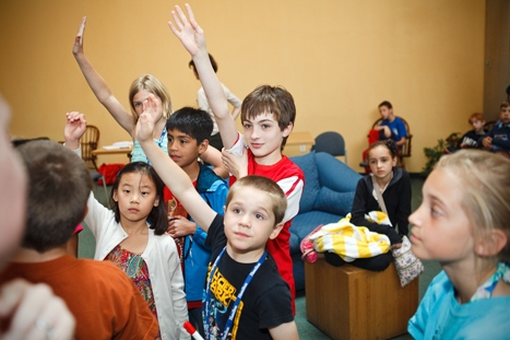 Children raise their hands to guess letters during a game of hangman at kid's camp on Saturday, June 2, 2012.