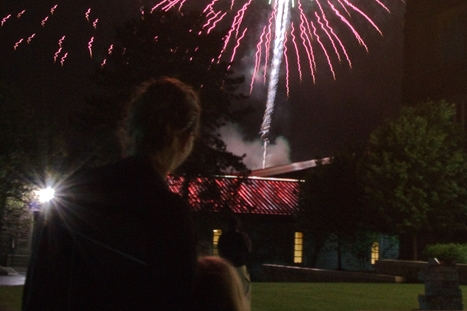 Fireworks explode over the fieldhouse as spectators watch during reunion weekend.