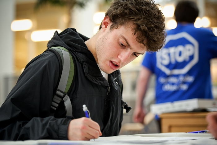 James Kruger '12 signs a thank you card in Kirner-Johnson.