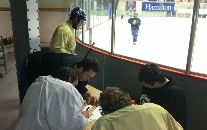The men's hockey team signs thank you cards during practice on Thursday, February 23, 2012.