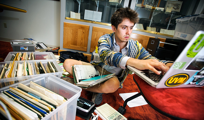Will Newman '14 sorts and organizes a large cache of materials by the late poet Agha Shahid Ali in Burke Library's Special Collections.