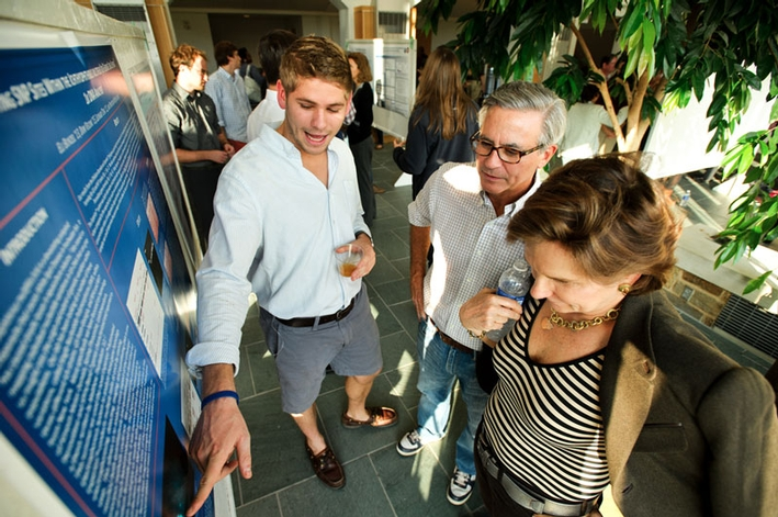 Eli Bunzel '13 explains his research to his parents, Jeff and Mary-Elizabeth. (PHOTO BY NANCY L. FORD)