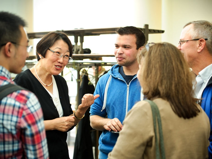 Professor Hong Gang Jin talks with Kevin Rovelli '15 and his parents, Dan Rovelli and Ana Paula Machado.  (PHOTO BY NANCY L. FORD)