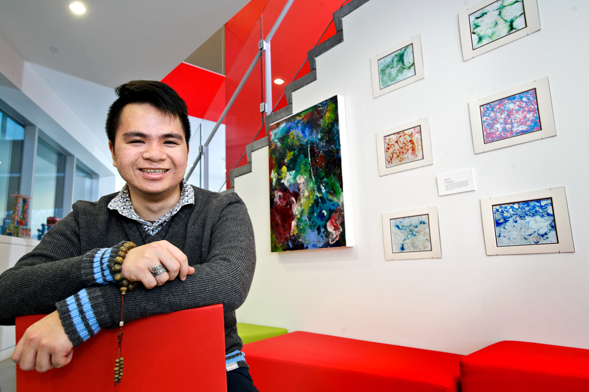 Minh Nguyen '17 poses with some of his work in the Kennedy Center.