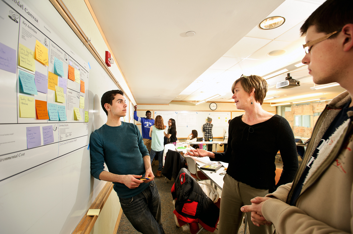 Michael Nelson '16 left, and Alexandru Hirsu '17 speak with Anke Wessels, of Cornell University, center, as they work on a project together during the Levitt Social Innovation Fellows Program.